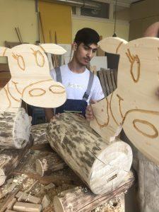 Die Köpfe werden in die Holzstämme eingesetzt.